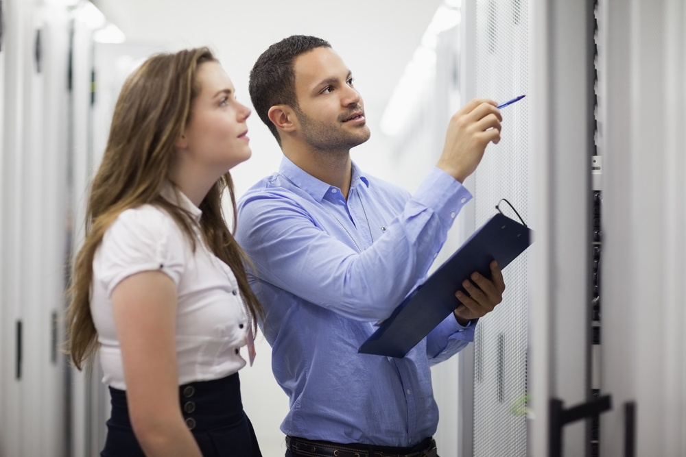 Technicians with clipbard looking at servers in data center.jpeg