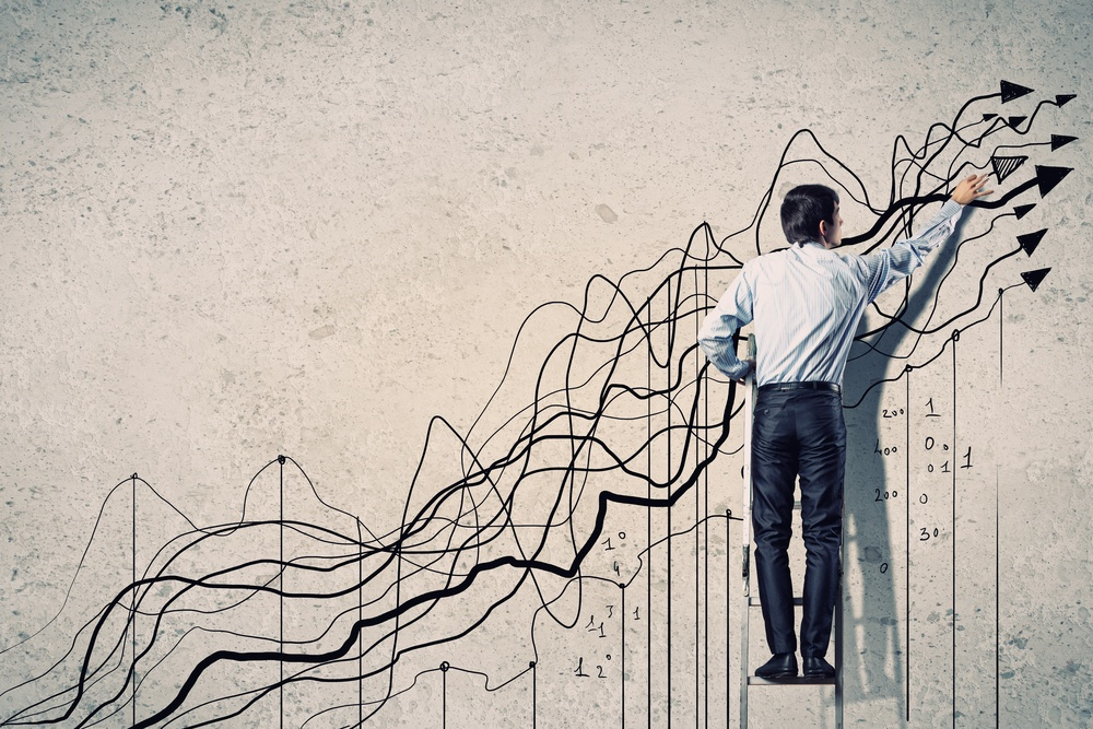 Back view image of businessman drawing graphics on wall.jpeg
